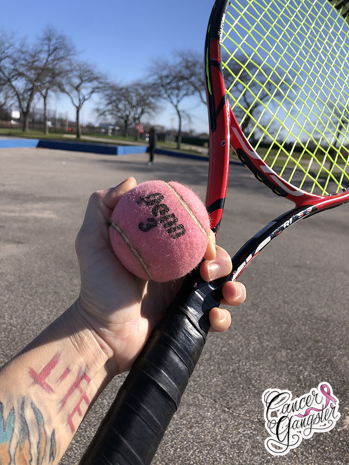 Tennis racket and ball at park